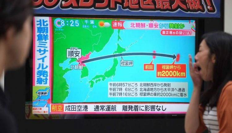 01 Japoneses observan en una pantalla imagen de la trayectoria del misil. (AFP-JiJI)